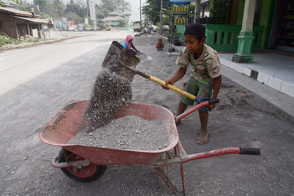 . An Indonesian child collects sand and gravel, following the volcanic eruption of Mount Kelud in East Java on February 13, in Kediri on February 16, 2014. The volcanic Mount Kelud erupted in East Java on February 13.  AFP PHOTO/JUNI  KRISWANTO/AFP/Getty Images