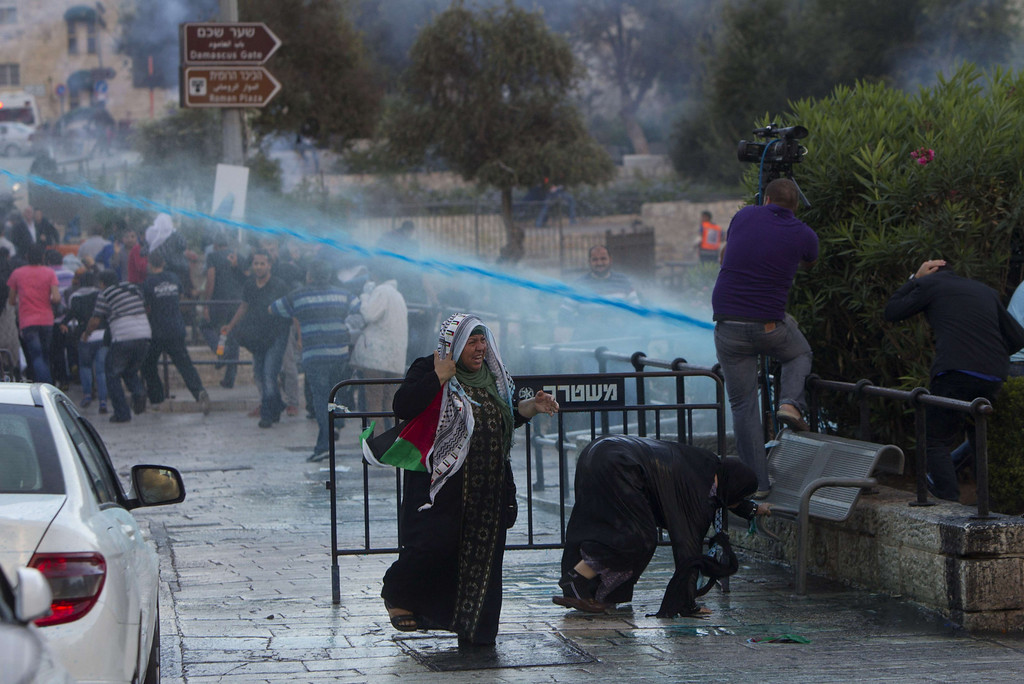 . Palestinians run for cover from water being sprayed by Israeli security forces to disperse demonstrators in front of Damascus gate leading to the old city of Jerusalem on September 24, 2013 during a protest against the old city being fenced off due to the Jewish celebration of Sukkot. The Sukkot (Tabernacles) is a biblical Jewish holiday on which Hebrews make a pilgrimage to a temple in Jerusalem.  AHMAD GHARABLI/AFP/Getty Images