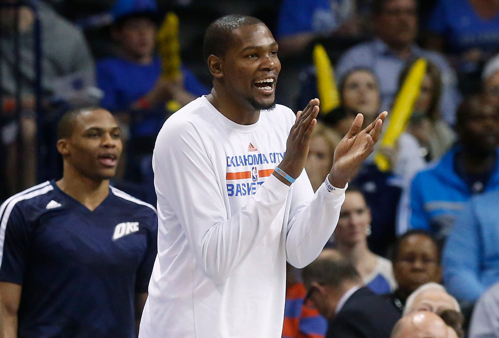 . Oklahoma City Thunder forward Kevin Durant, right, and guard Russell Westbrook, left, cheer from the bench in the fourth quarter of an NBA basketball game against the Denver Nuggets in Oklahoma City, Monday, March 24, 2014. Oklahoma City won 117-96. (AP Photo/Sue Ogrocki)
