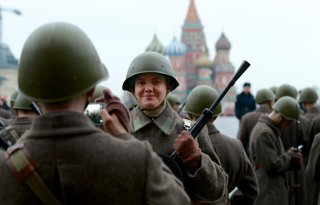 . A Russian soldiers dressed in Red Army World War II uniform poses for a photo while preparing to parade in Red Square, in front of St. Basil Cathedral in Moscow, Russia, Thursday, Nov. 7, 2013.. Thousands of Russian soldiers and military cadets marched across Red Square to mark the 72nd anniversary of a historic World War II parade. The show honored the participants of the Nov. 7, 1941 parade who then headed directly to the front to defend Moscow from the Nazi forces. The parade Monday involved about 6,000 people, many of them dressed in World War II-era uniforms. (AP Photo/Alexander Zemlianichenko)