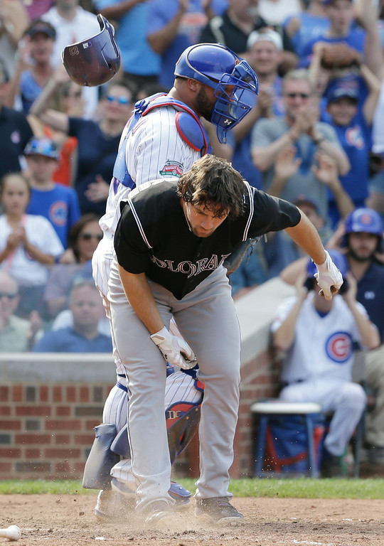 . Colorado Rockies\' Charlie Culberson, front, throws his helmet after being called out on strikes during the ninth inning of a baseball game against the Chicago Cubs in Chicago, Thursday, July 31, 2014. The Cubs won 3-1. (AP Photo/Nam Y. Huh)