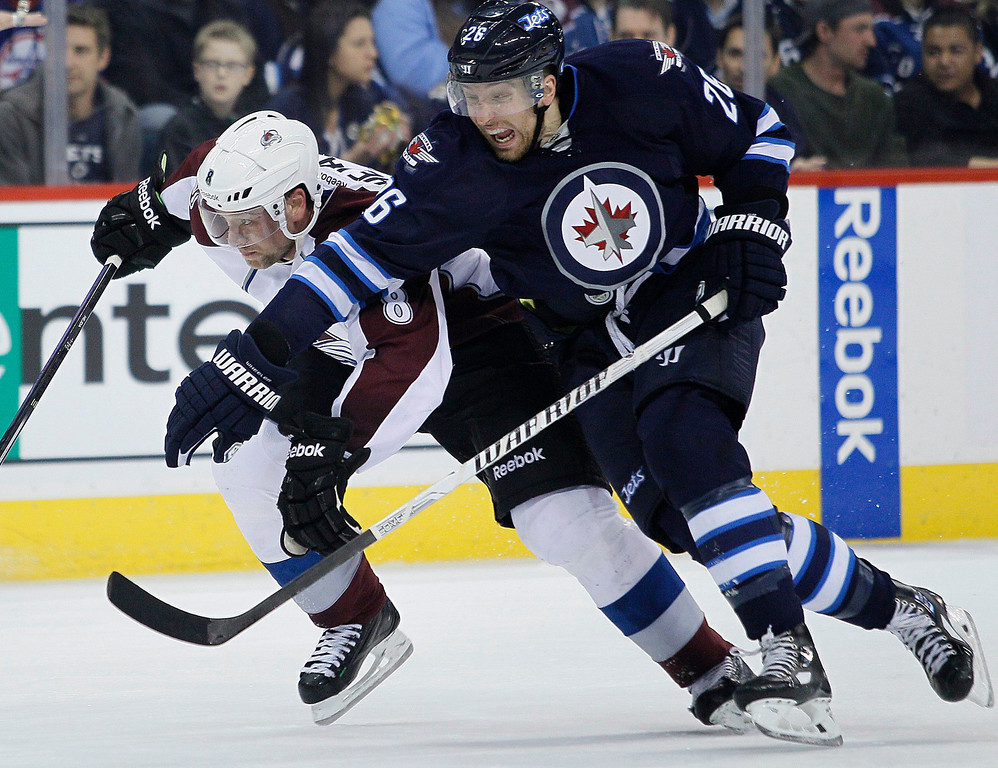 . Winnipeg Jets\' Blake Wheeler (26) attempts to get around Colorado Avalanche\'s Jan Hejda (8) as they drive for the puck during the second period of an NHL hockey game Wednesday, March 19, 2014, in Winnipeg, Manitoba. (AP Photo/The Canadian Press, John Woods)