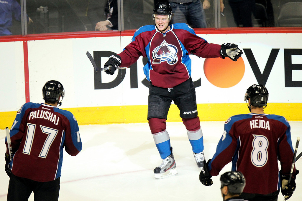 . Colorado Avalanche\'s Jamie McGinn, top, celebrates a goal with Aaron Palushaj (17) and Jan Hejda (8) during the first period of an NHL hockey game against the St. Louis Blues, Sunday, April 21, 2013, in Denver. (AP Photo/Barry Gutierrez)