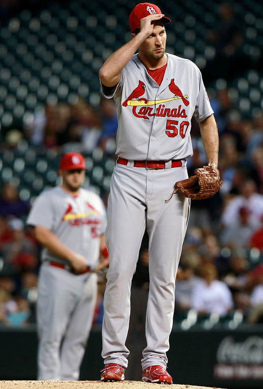 . St. Louis Cardinals starting pitcher Adam Wainwright adjusts his cap after giving up a single to Colorado Rockies\' Troy Tulowitzki that drove in two runs in the first inning of a baseball game in Denver on Wednesday, Sept. 18, 2013. (AP Photo/David Zalubowski)