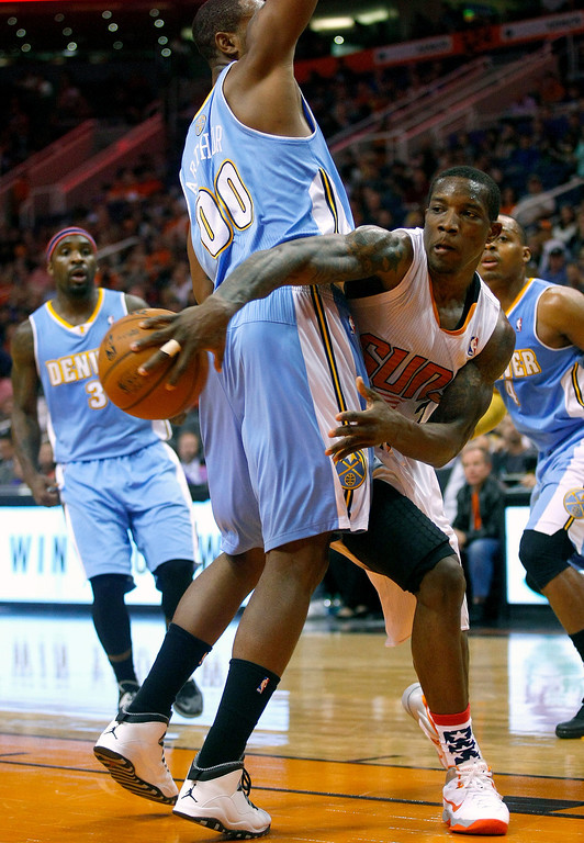 . Phoenix Suns point guard Eric Bledsoe (2), right, makes the pass around the back of Denver Nuggets power forward Darrell Arthur (00) in the fourth quarter during an NBA basketball game on Friday, Nov. 8, 2013, in Phoenix. The Suns defeated the Nuggets 114-93. (AP Photo/Rick Scuteri)