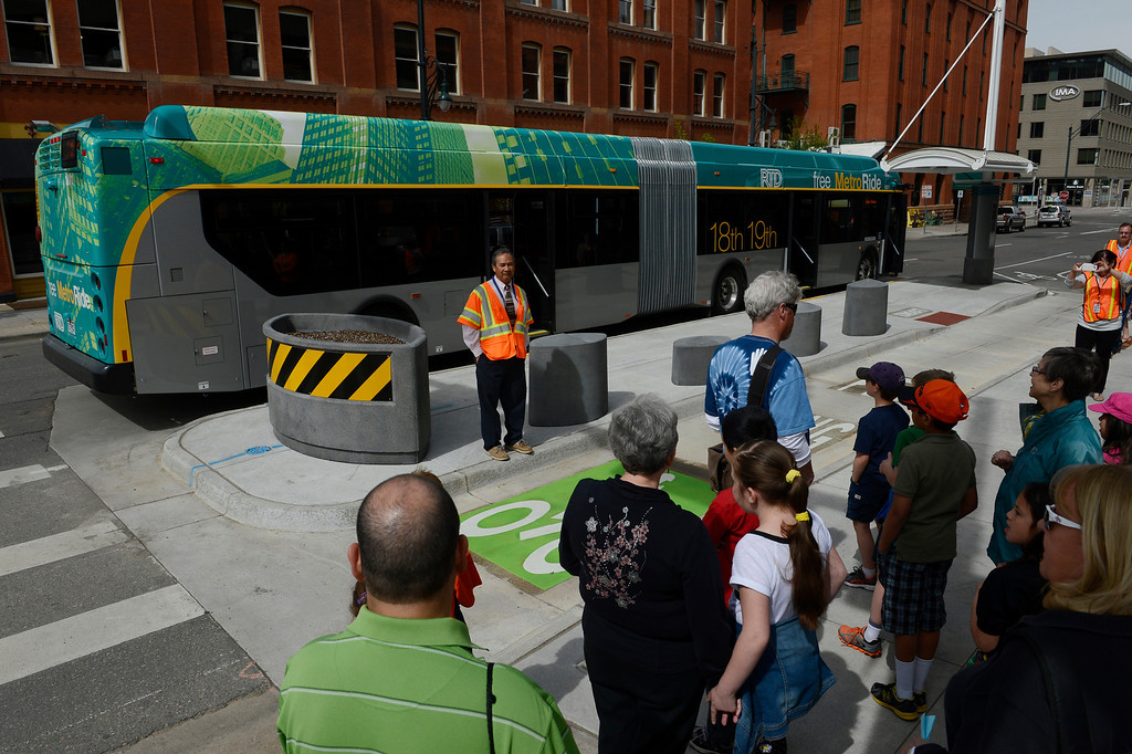 . DENVER, CO. - APRIL 25: TRD Denver Union Station project manager, Jerome Nery, talks with a group of folks in front of the new RTD Free MetroRide bus parked at 18th and Wazee Friday morning, April 25, 2014. This free bus service, which begins May 12, 2014, originates from Union Station, heads east up 19th Ave to Broadway, turns at 16th to Lincoln and then heads back to the station with various stops throughout before making it\'s way back to the Union Station Transit Center. (Photo By Andy Cross / The Denver Post)