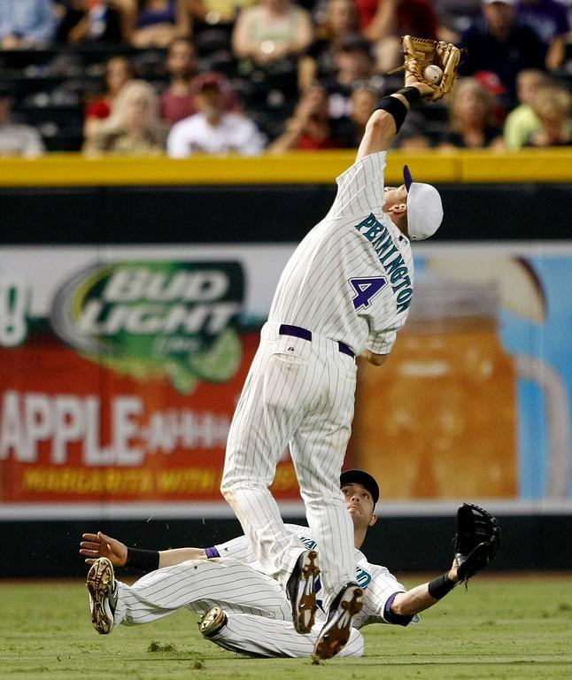 . Arizona Diamondbacks shortstop Cliff Pennington (4) makes a catch over left fielder Nolan Reimoid in the third inning during a baseball game against the Colorado Rockies, Saturday, Aug. 30, 2014, in Phoenix. (AP Photo/Rick Scuteri)