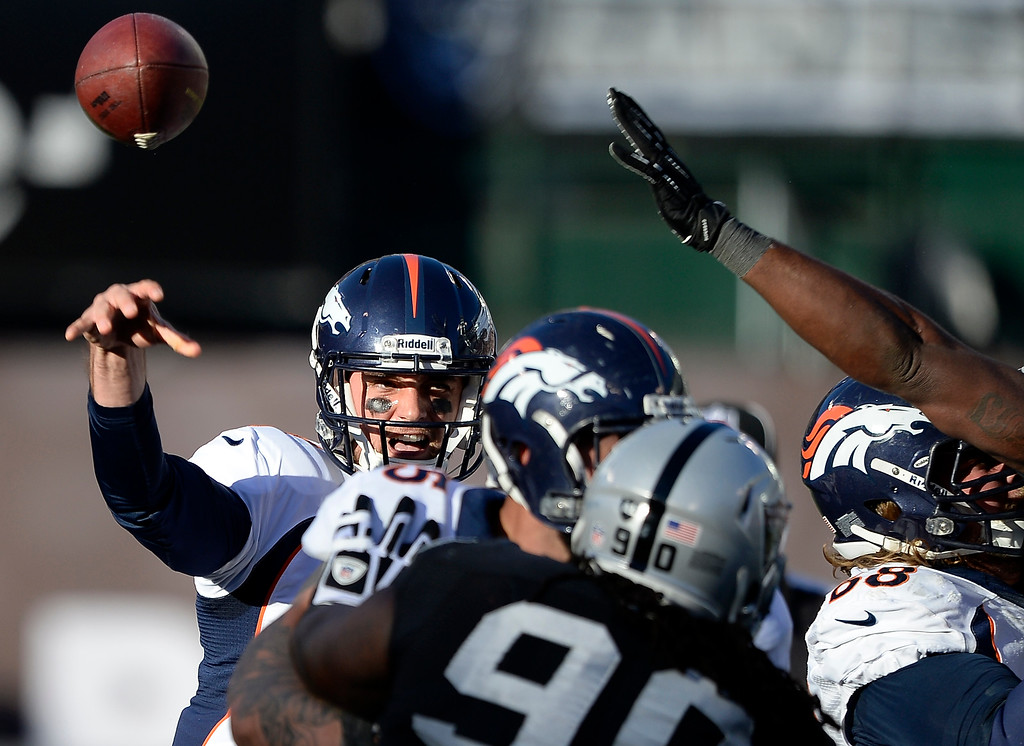 . Denver Broncos quarterback Brock Osweiler (17) throws a pass over the Oakland Raiders defense during the third quarter at O.co Coliseum. (Photo by John Leyba/The Denver Post)
