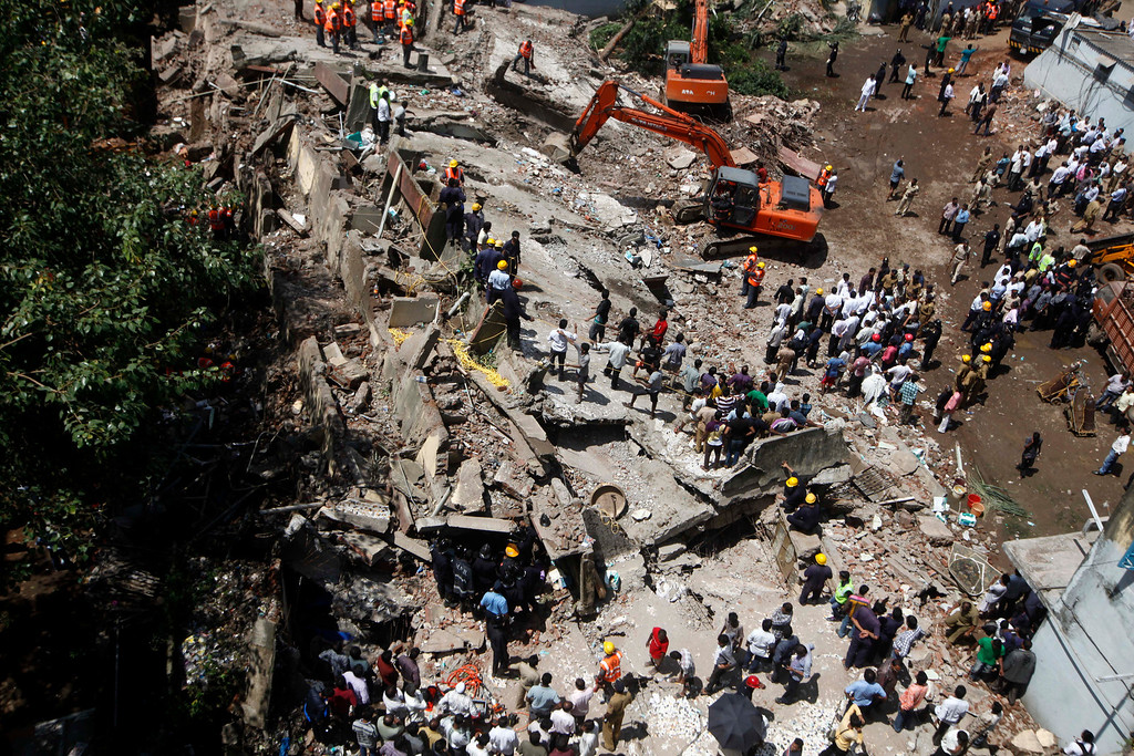 . Rescue workers look for survivors and clear debris at the site of a building that collapsed in Mumbai, India, Friday, Sept. 27, 2013.  (AP Photo/Rajanish Kakade)