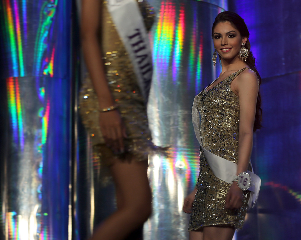 . Marcelo Ohio of Brazil, right, competes in the evening gown competition with contestant Nethnapada Kanrayanon, in the foreground, at the Miss International Queen 2013 transgender beauty pageant  in Pattaya, Thailand Friday, Nov. 1, 2013. (AP Photo/Apichart Weerawong)