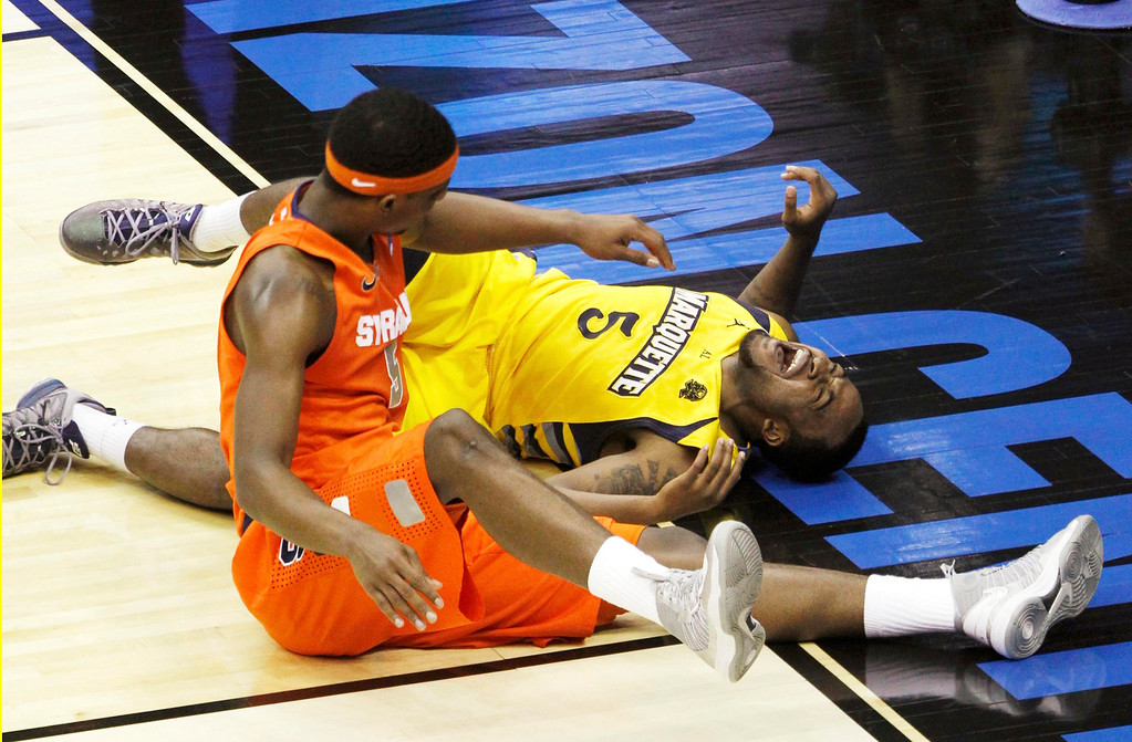 . Marquette Golden Eagles guard Junior Cadougan (R) screams after he was injured by Syracuse Orange forward C.J. Fair during the first half in their East Regional NCAA men\'s basketball game in Washington, March 30, 2013. REUTERS/Gary Cameron