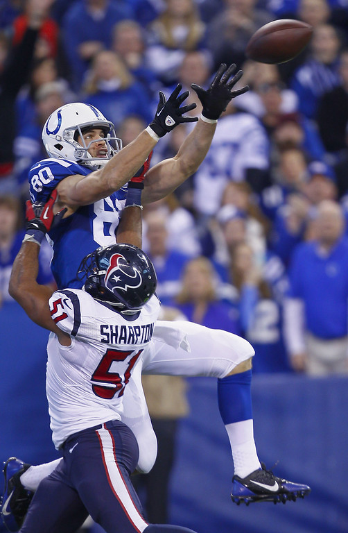 . Coby Fleener #80 of the Indianapolis Colts goes up for a pass while defended by Darryl Sharpton #51 of the Houston Texans at Lucas Oil Stadium on December 15, 2013 in Indianapolis, Indiana. (Photo by Michael Hickey/Getty Images)