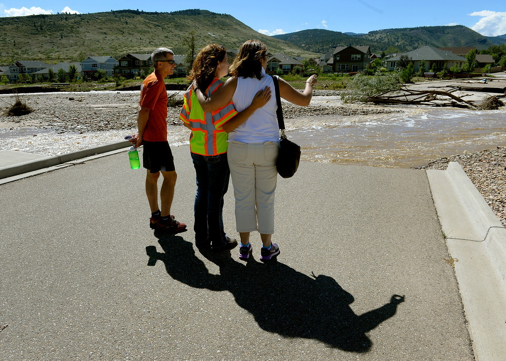 . LYONS, CO. - SEPTEMBER 18: (l-r) Mayor pro tem Kirk Udovich, Town administrator Victoria Simonsen and Mayor Julie VanDomlen look over damage where the McConnell Bridge was washed away by flooding in Lyons,  CO September 18, 2013. VanDomlen had just returned from Africa and was seeing the town for the first time. Management. Business owners were allowed to return to town today and residents will be allowed to their homes tomorrow. As emergency personnel methodically make their way from door-to-door of flooded and damaged homes this week, the number of unaccounted-for Coloradans is dropping. The number in Boulder County has fallen to four. (Photo By Craig F. Walker / The Denver Post)