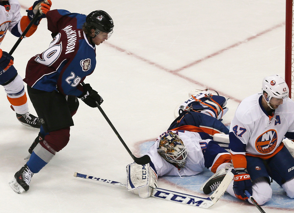 . Colorado Avalanche center Nathan MacKinnon, left, has his shot stopped by New York Islanders goalie Kevin Poulin, center, as defenseman Andrew MacDonald looks for the puck during the second period of an NHL hockey game in Denver on Friday, Jan. 10, 2014. (AP Photo/David Zalubowski)