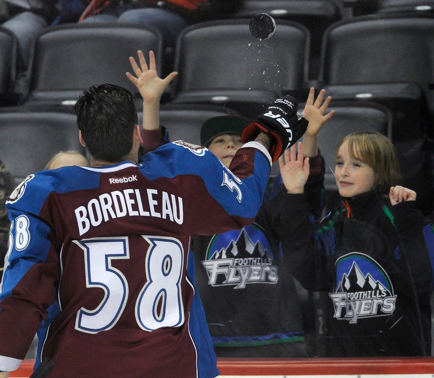 . Denver wing Patrick Bordeleau tossed a puck over the glass to a pair of fans before the game.    Photo By Karl Gehring/The Denver Post