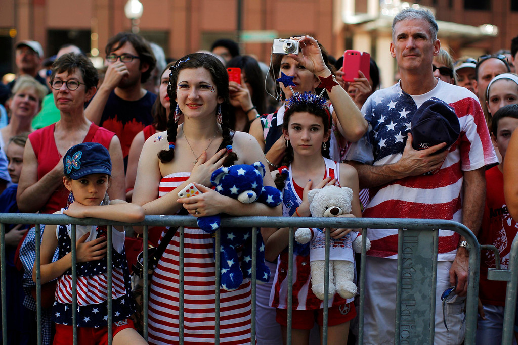 . The Haig family stands for the United States pledge of allegiance before a public reading the United States Declaration of Independence, part of Fourth of July Independence Day celebrations, in Boston, Massachusetts July 4, 2013. People across the United States gathered on Thursday for parades, picnics and fireworks at Independence Day celebrations, held under unprecedented security following the Boston Marathon bombings. Spectators waving U.S. flags and wearing red, white and blue headed for public gatherings in Boston, New York, Washington, Atlanta and other cities under the close watch of police armed with hand-held chemical detectors, radiation scanners and camera surveillance, precautions sparked by the deadly April 15 bombings.     REUTERS/Brian Snyder