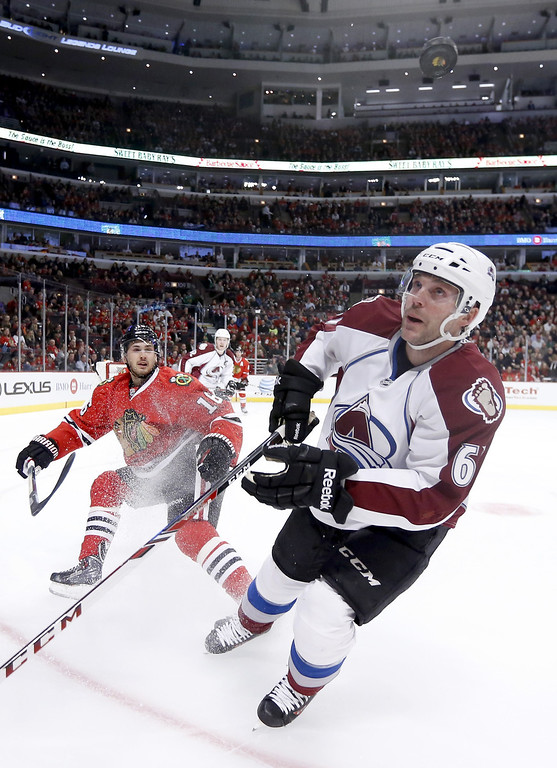 . Chicago Blackhawks center Marcus Kruger (16) and Colorado Avalanche defenseman Andre Benoit (61) keep an on a flying puck during the first period of an NHL hockey game Tuesday, March 4, 2014, in Chicago. (AP Photo/Charles Rex Arbogast)
