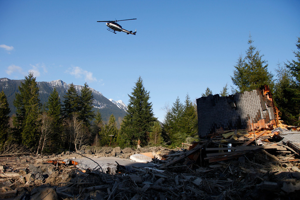 . A helicopter flies low over the mudslide effected area Sunday, March 23, 2014, in Oso, Wash. (AP Photo /The Herald, Genna Martin)