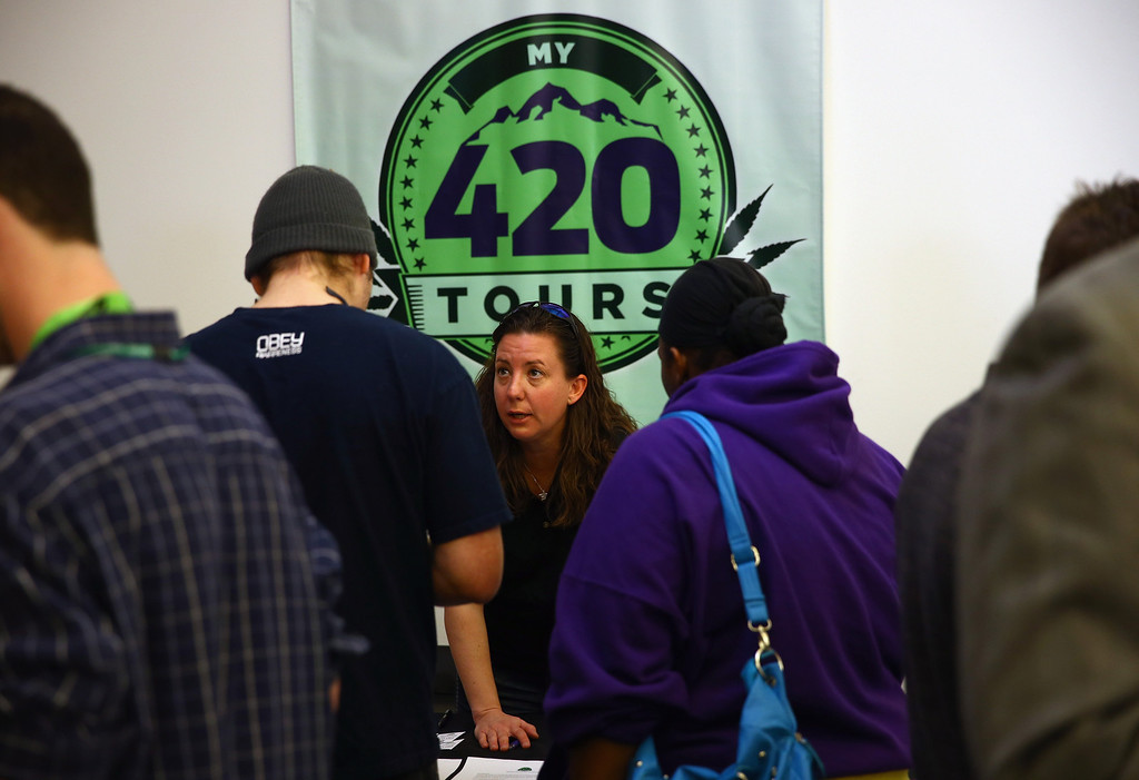 . Jennifer Morton of My 420 Tours talks with job seekers at CannaSearch, Colorado\'s first cannabis job fair, on March 13, 2014 in Denver, Colorado. O.PenVAPE, the largest national brand in cannabis, held the first of its kind Cannabis Job Fair hoping to match applicants with businesses in the Colorado marijuana industry.  (Photo by Doug Pensinger/Getty Images)