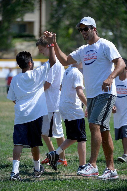 . Eric Decker gets a high five after throwing a bomb down field for a touchdown during football camp. Demaryius Thomas and Eric Decker team up with ProCamps for their football camp held at Littleton High School July 11, 2013.  (Photo By John Leyba/The Denver Post)