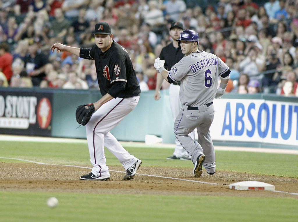 . Trevor Cahill #35 of the Arizona Diamondbacks (L) watches as the ball rolls away after being unable to field an under hand throw by first baseman Mark Trumbo #15 (C) as Corey Dickerson #6 of the Colorado Rockies is safe at first during the first inning of a MLB game at Chase Field on August 9, 2014 in Phoenix, Arizona.  (Photo by Ralph Freso/Getty Images)