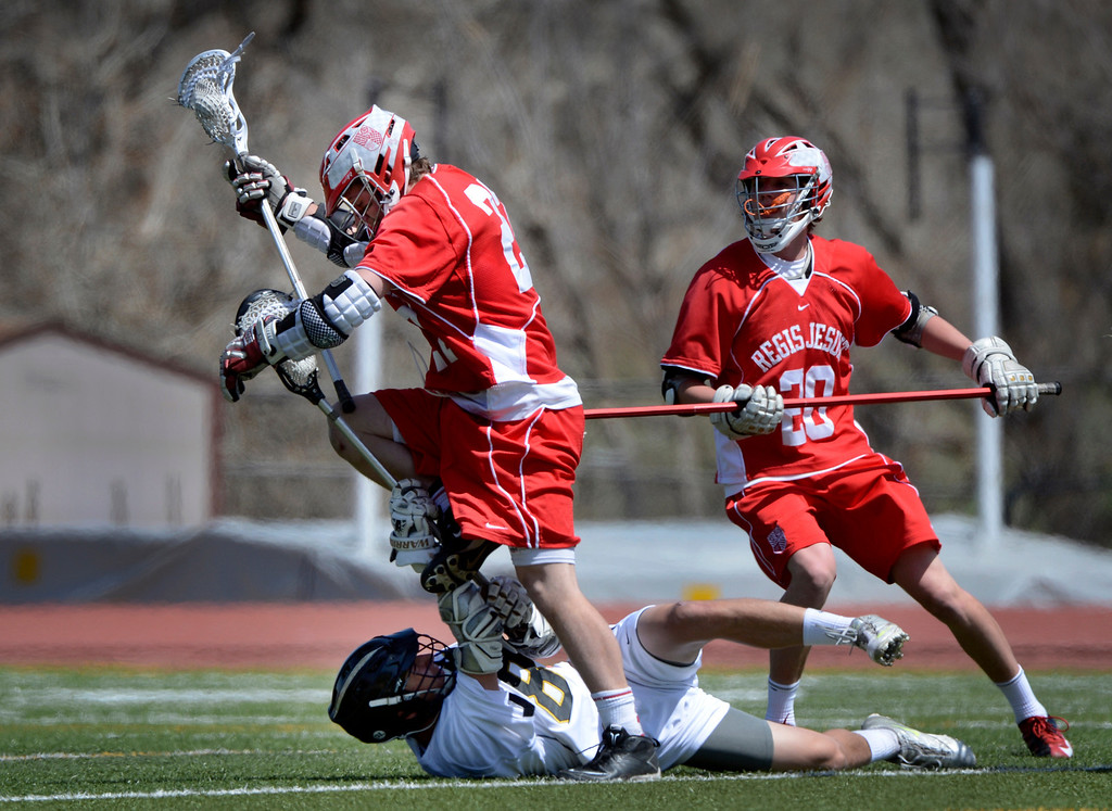 . LITTLETON, CO. - MAY 04:  Regis Jesuit\'s Alec Barnes jumps over Arapahoe\'s Ben Eigner during the varsity high school lacrosse game between the Arapahoe Warriors and the Regis Jesuit Raiders in Littleton, CO May 04, 2013. The Raiders won the game 9-6.  (Photo By Craig F. Walker/The Denver Post)