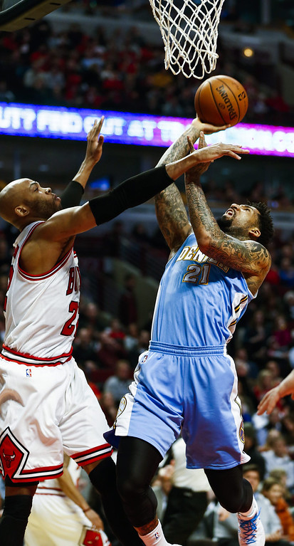 . Denver Nuggets forward Wilson Chandler (R) shoots over Chicago Bulls forward Taj Gibson (L) in the first half of their NBA game at the United Center in Chicago, Illinois, USA, 21 February 2014.  EPA/TANNEN MAURY