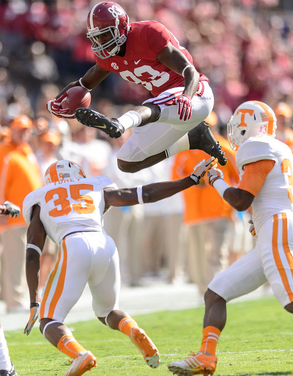 . Alabama wide receiver Kevin Norwood (83) hurdles Tennessee defensive back JaRon Toney (35) during the first quarter of an NCAA college football game, Saturday, Oct. 26, 2013, at Bryant-Denny Stadium in Tuscaloosa, Ala. (AP Photo/AL.com, Vasha Hunt)