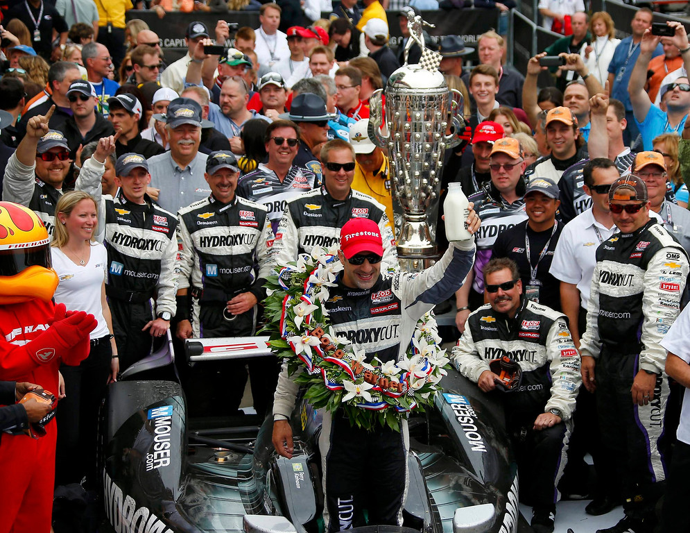 . KV Racing Technology driver Tony Kanaan of Brazil takes a traditional drink of milk as he celebrates with his crew and the Borg Warner Trophy after winning the 97th running of the Indianapolis 500 at the Indianapolis Motor Speedway in Indianapolis, Indiana, May 26, 2013.  REUTERS/Jeff Haynes