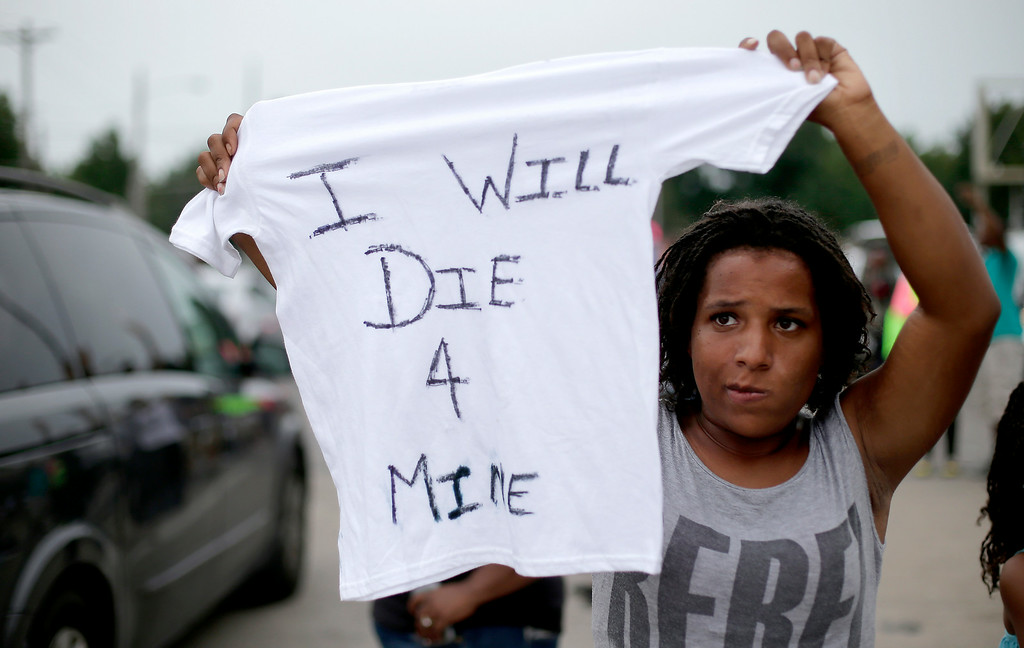 . Chelsea Johnson, from St. Louis, holds up a shirt protesting the shooting death of Michael Brown by police nearly a week ago in Ferguson, Mo., Friday, Aug. 15, 2014, in Ferguson, Mo. (AP Photo/Charlie Riedel)