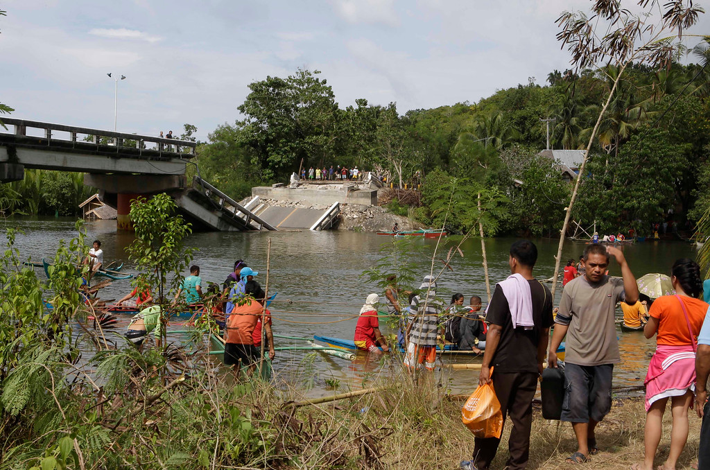 . Residents board small boats to get to the other side amidst a collapsed bridge at Cortes township, Bohol province in central Philippines, Wednesday Oct. 16, 2013. (AP Photo/Bullit Marquez)