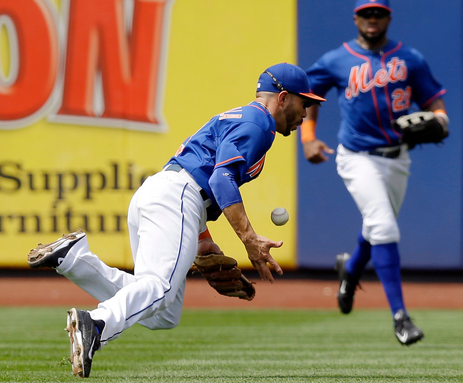 . New York Mets left fielder Eric Young Jr., right, watches as shortstop Omar Quintanilla loses the ball on a single hit by Colorado Rockie\'s Nolan Arenado during the seventh inning of a baseball game against the Colorado Rockies in New York, Thursday, Aug. 8, 2013. The Mets won 2-1. (AP Photo/Kathy Willens)