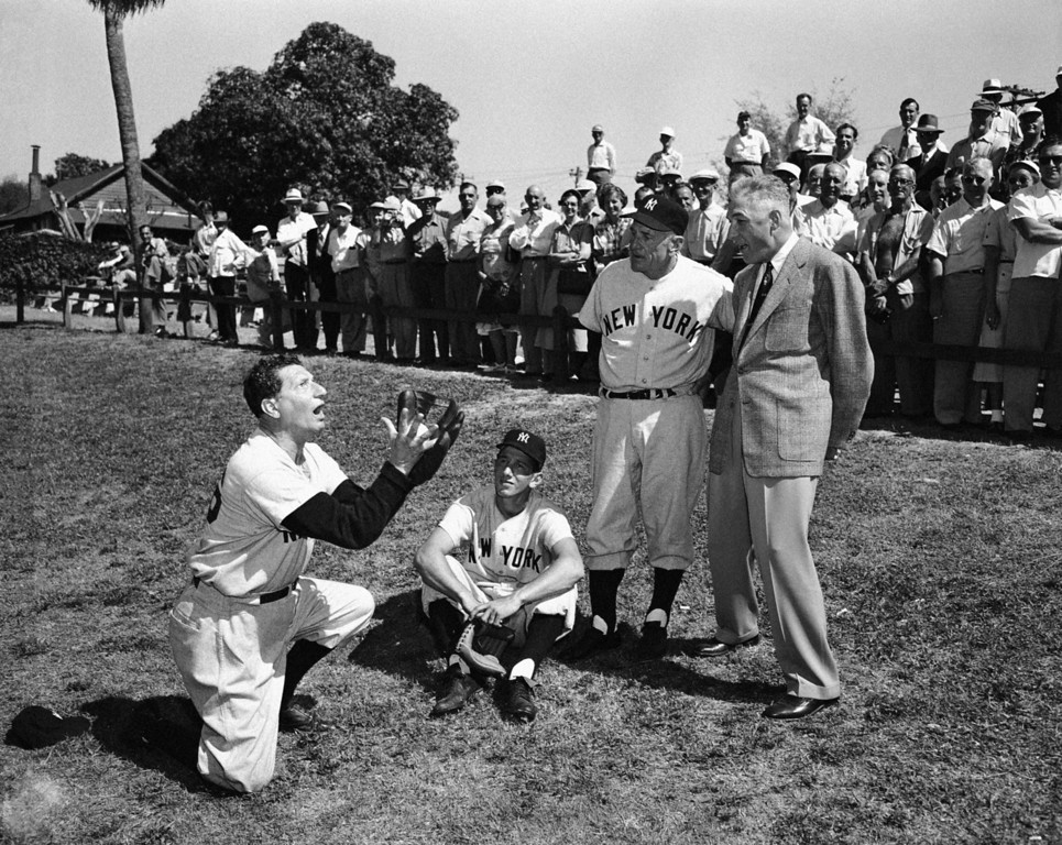 . Al Schacht, left, demonstrates how Billy Martin, seated, made a game-saving catch in the last fall\'s World Series, March 3, 1953, at the Yankees\' spring training camp in St. Petersburg, Florida.  Manager Casey Stengel and baseball commissioner Ford Frick look on. (AP Photo/Harry Harris)