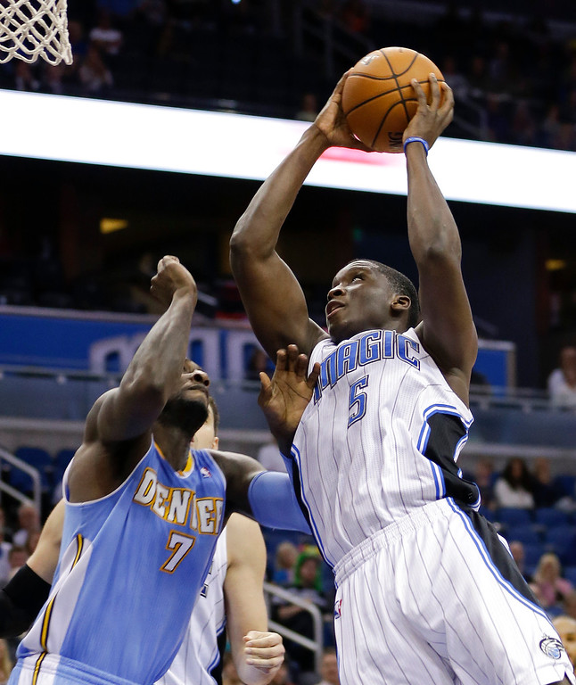 . Orlando Magic\'s Victor Oladipo (5) goes to the basket for a shot as Denver Nuggets\'s J.J. Hickson (7) tries to defend during the second half of an NBA basketball game in Orlando, Fla., Wednesday, March 12, 2014. Denver won 120-112. (AP Photo/John Raoux)