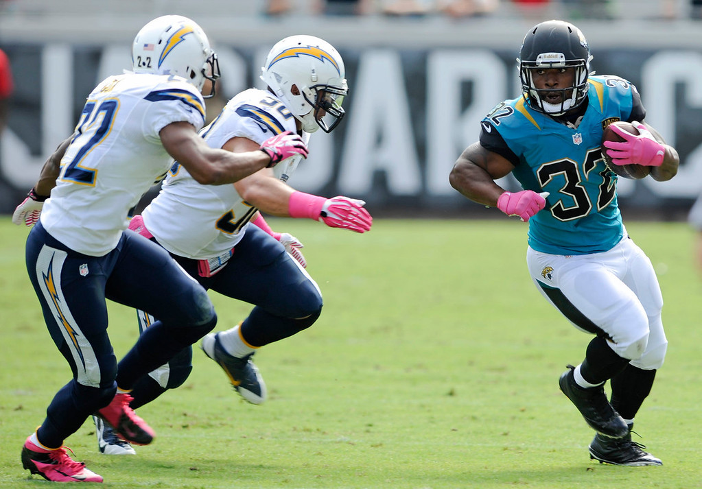 . Jacksonville Jaguars running back Maurice Jones-Drew (32) gains yardage as he tries to get past San Diego Chargers cornerback Derek Cox, left, and inside linebacker Manti Te\'o (50) during the first half of an NFL football game in Jacksonville, Fla., Sunday, Oct. 20, 2013.(AP Photo/Stephen Morton)