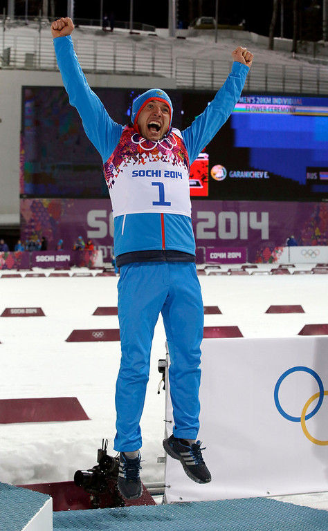 . Bronze medalist Russia\'s Yevgeny Garanichev jumps in celebration during the flowers ceremony for the men\'s biathlon 20k individual race, at the 2014 Winter Olympics, Thursday, Feb. 13, 2014, in Krasnaya Polyana, Russia. (AP Photo/Lee Jin-man)