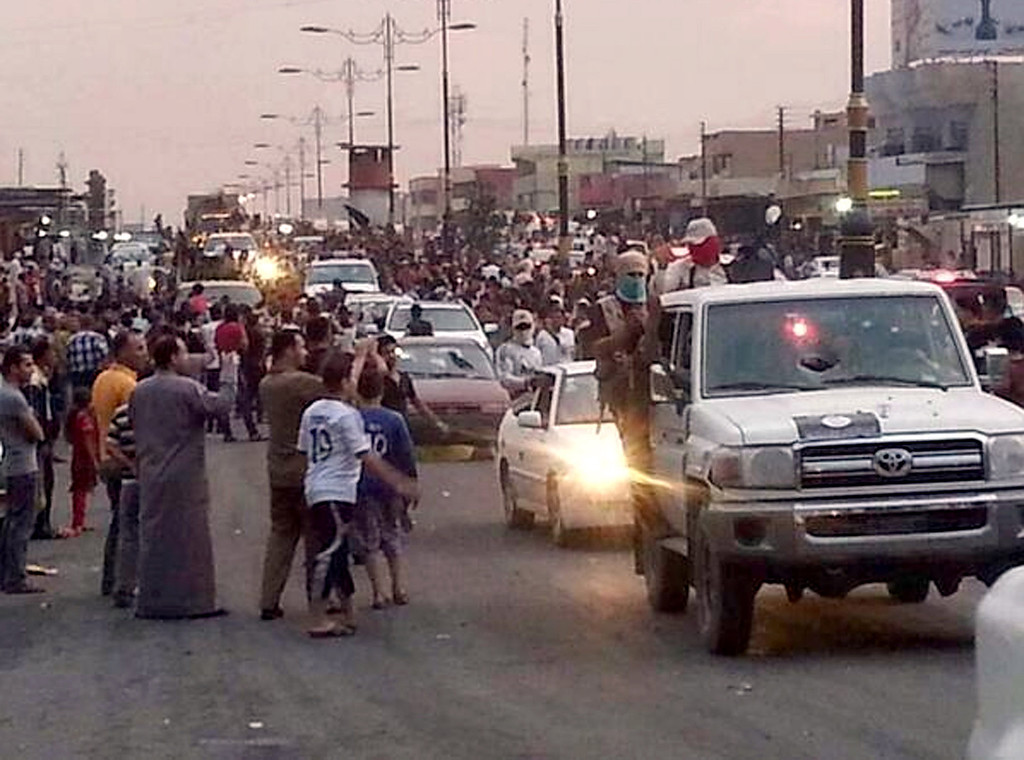 . In this file still image posted on a militant Twitter account on Wednesday, June 11, 2014, which has been authenticated based on its contents and other AP reporting, militants parade down a main road in Mosul, Iraq. Days after Iraqís second-largest city fell to al-Qaida-inspired fighters, some Iraqis are already returning to Mosul, lured back by insurgents offering cheap gas and food, restoring power and water and removing traffic barricades. (AP Photo/militant source via Twitter, File)