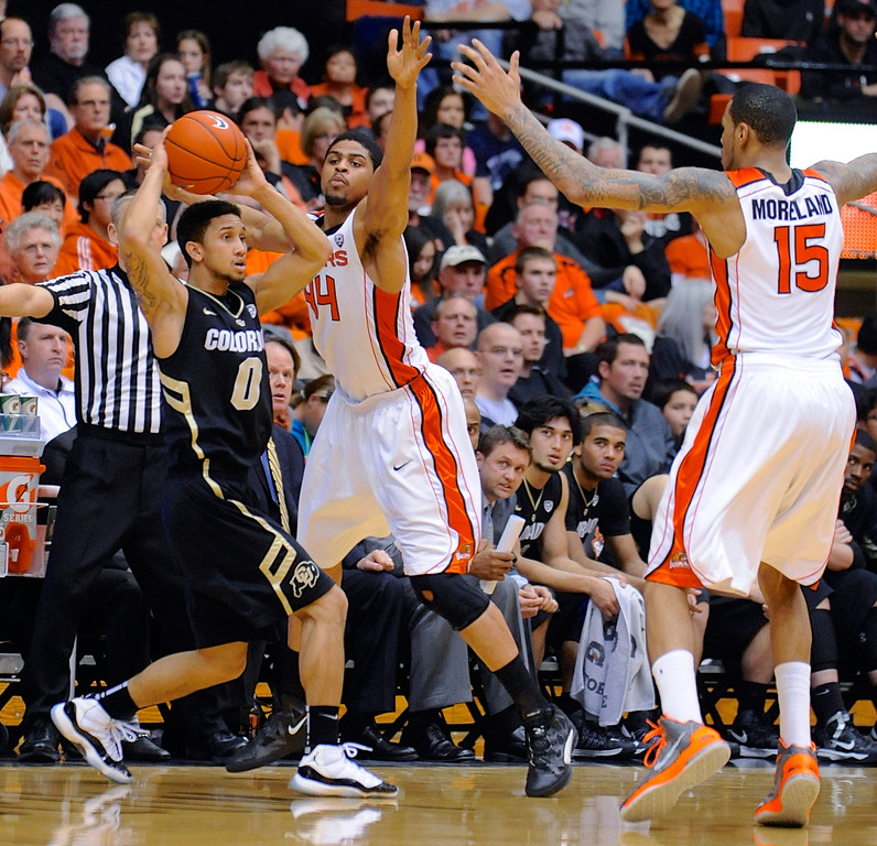 . Oregon State\'s Devon Collier (44) and Eric Moreland defend against Colorado\'s Askia Booker (0) during the second half of an NCAA college basketball game in Corvallis, Ore., Sunday, Feb. 10, 2013. Colorado won 72-68. (AP Photo/Greg Wahl-Stephens)