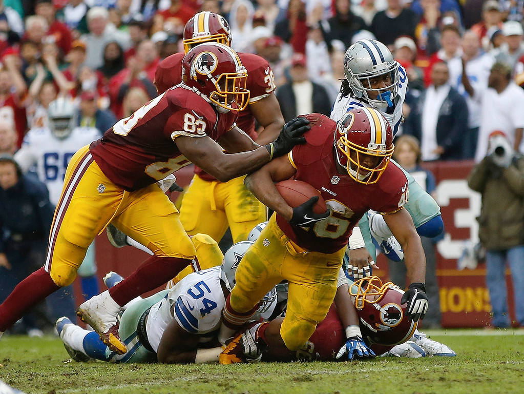 . Washington Redskins running back Alfred Morris is dragged down by Dallas Cowboys outside linebacker Bruce Carter (54) during the second half of an NFL football game in Landover, Md., Sunday, Dec. 22, 2013. (AP Photo/Evan Vucci)