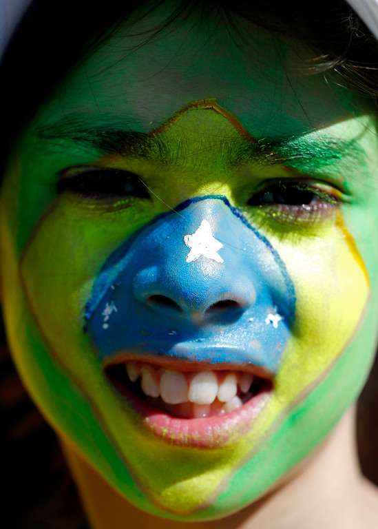 . Brazilian Gabriel Diz Vales De Gondra Santos, 11, whose face is painted to represent her country\'s national flag, waits to enter the Itaquerao Stadium to watch the World Cup opening match, between Brazil and Croatia of group A, in Sao Paulo, Brazil, Thursday, June 12, 2014.  (AP Photo/Julio Cortez)