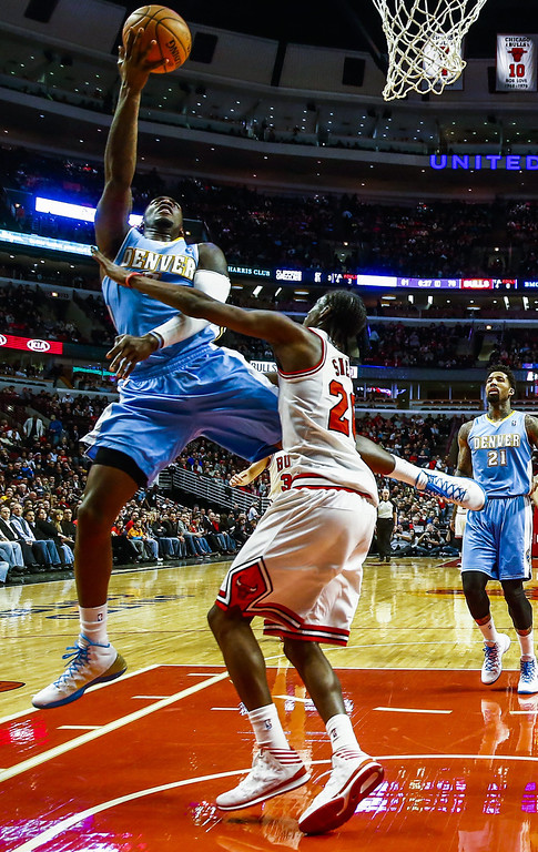 . Denver Nuggets center J.J. Hickson (L) shoots over Chicago Bulls forward Tony Snell (R) in the second half of their NBA game at the United Center in Chicago, Illinois, USA, 21 February 2014. The Bulls defeated the Nuggets.  EPA/TANNEN MAURY