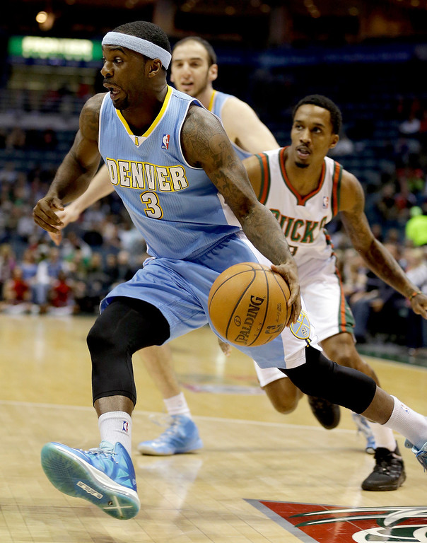 . Denver Nuggets\' Ty Lawson (3) drives past Milwaukee Bucks\' Brandon Jennings, right, during the first half of an NBA basketball game, Monday, April 15, 2013, in Milwaukee. (AP Photo/Jeffrey Phelps)