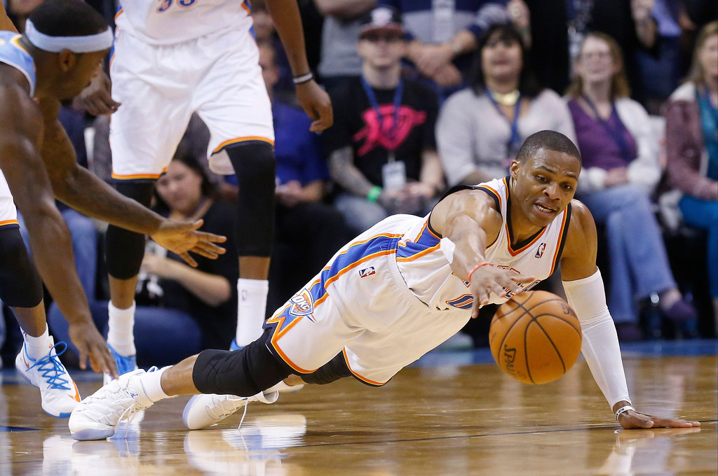 . Oklahoma City Thunder guard Russell Westbrook (0) dives for a loose ball in front of Denver Nuggets guard Ty Lawson (3) in the fourth quarter of an NBA basketball game in Oklahoma City, Monday, Nov. 18, 2013. Oklahoma City won 115-113. (AP Photo/Sue Ogrocki)