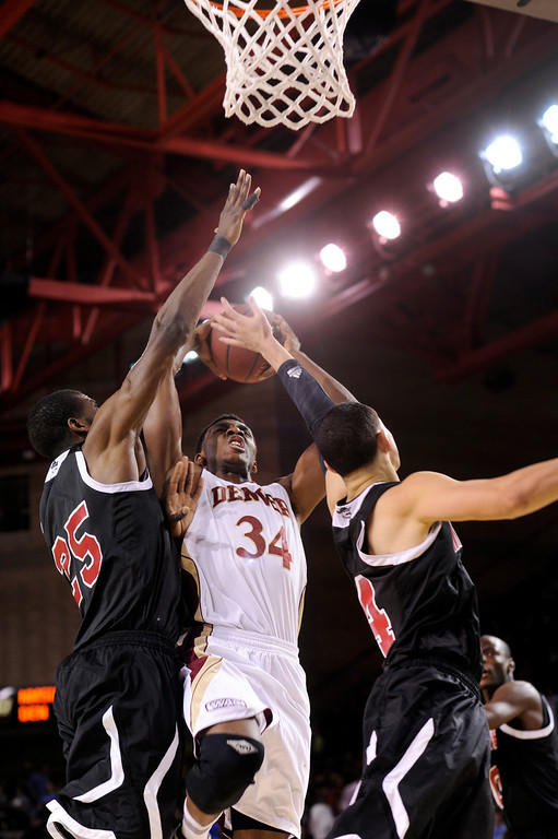. DENVER, CO. - MARCH 2: Pioneers forward Chris Udofia (34) drove the lane between Aggies junior Renaldo Dixon (25) and sophomore Terrel de Rouen (14) in the first half. The University of Denver men\'s basketball team hosted New Mexico State Saturday afternoon, March 2, 2013 at Magness Arena. (Photo By Karl Gehring/The Denver Post)