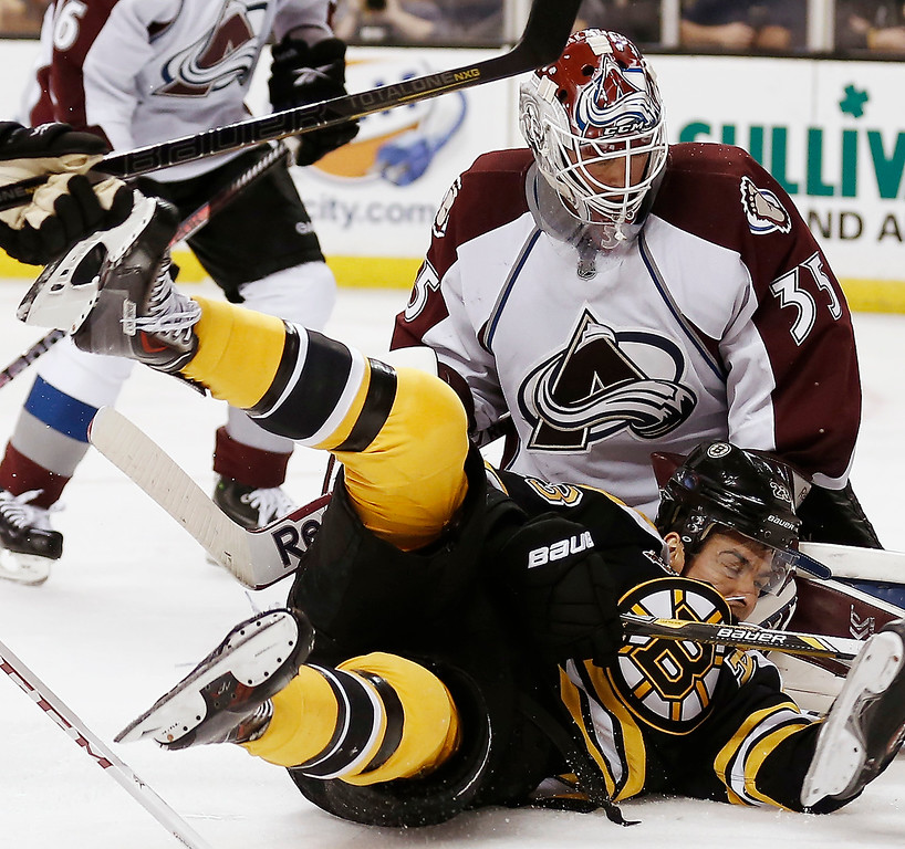 . Boston Bruins\' Chris Kelly is sent to the ice in front of Colorado Avalanche goalie Jean-Sebastien Giguere during the second period of an NHL hockey game in Boston on Thursday, Oct. 10, 2013. (AP Photo/Winslow Townson)