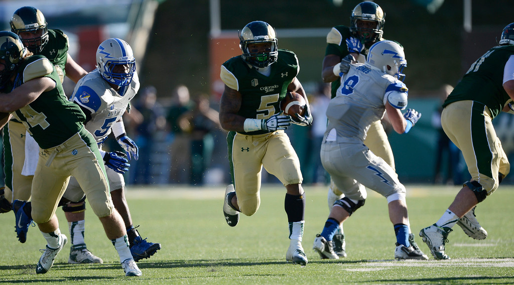 . Colorado State RB, Kapri Bibbs, center, finds a hole through Air Force defenders in the third quarter at Hughes Stadium Saturday afternoon, November 30, 2013. The Rams won 58-13. (Photo By Andy Cross/The Denver Post)