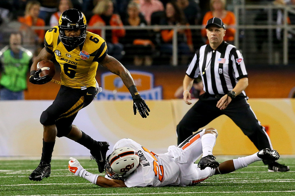 . ARLINGTON, TX - JANUARY 03:  Running back Marcus Murphy #6 of the Missouri Tigers runs the ball against Miketavius Jones #24 of the Oklahoma State Cowboys in the first half during the AT&T Cotton Bowl on January 3, 2014 in Arlington, Texas.  (Photo by Ronald Martinez/Getty Images)