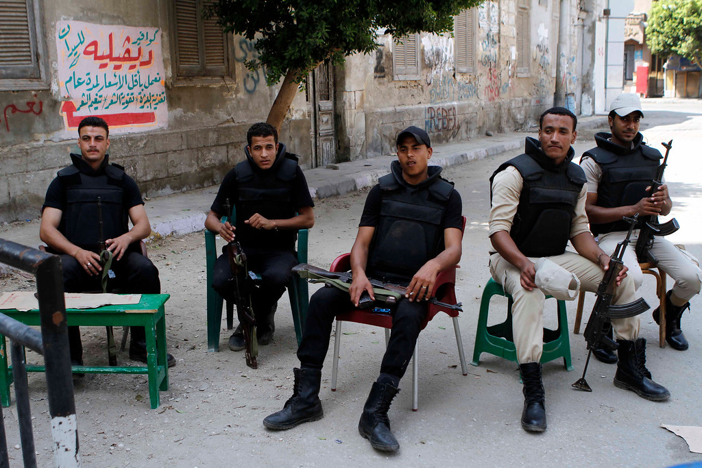 . Egyptian security forces take a break as they prepare to watch the area in Beni Sueif, south of Cairo, Egypt, Friday, Aug. 30, 2013. Security has been beefed up across the country in anticipation of the protests. The Brotherhood has also called for sit-ins to protest the new interim leaders who took over after the military ousted President Mohammed Morsi. (AP Photo/Sabry Khaled, El-Shorouk)