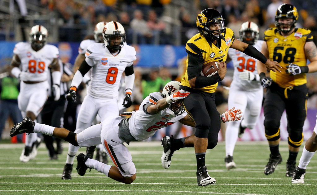 . ARLINGTON, TX - JANUARY 03:  Quarterback James Franklin #1 of the Missouri Tigers runs the ball for 16-yards against Lyndell Johnson #27 of the Oklahoma State Cowboys in the second quarter during the AT&T Cotton Bowl on January 3, 2014 in Arlington, Texas.  (Photo by Ronald Martinez/Getty Images)