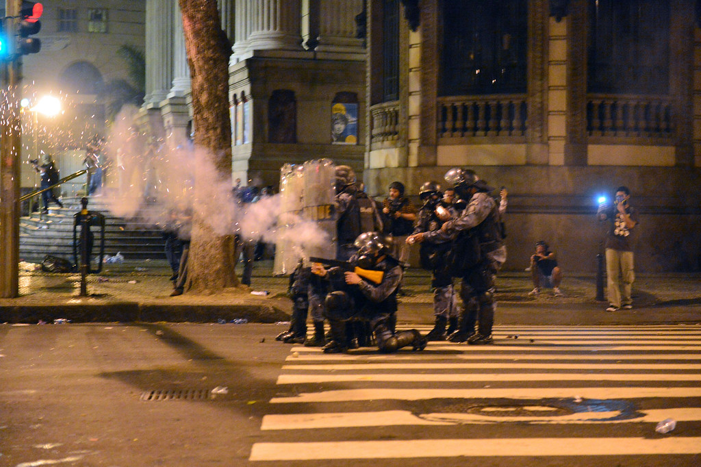 """. Policemen clash with demonstrator during the \""""Teachers\' day\"""" protest in demand of better working conditions and against police violence, on October 15, 2013 in Rio de Janeiro, Brazil. AFP PHOTO / CHRISTOPHE SIMON/AFP/Getty Images"""